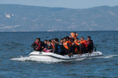 An inflatable boat filled with refugees and other migrants approaches the north coast of the Greek island of Lesbos. Turkey is visible in the background. More than 500,000 migrants have crossed by boat from Turkey to the Greek islands so far in 2015.