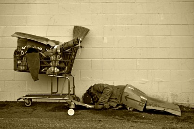 homeless man asleep on cardboard.