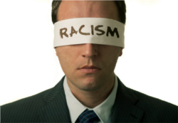 """Blindfolded man with """"racism"""" text on the blindfold"""